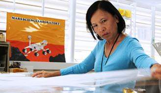 Lien Pham pulling material for a thermal blanket in JPL's shield shop